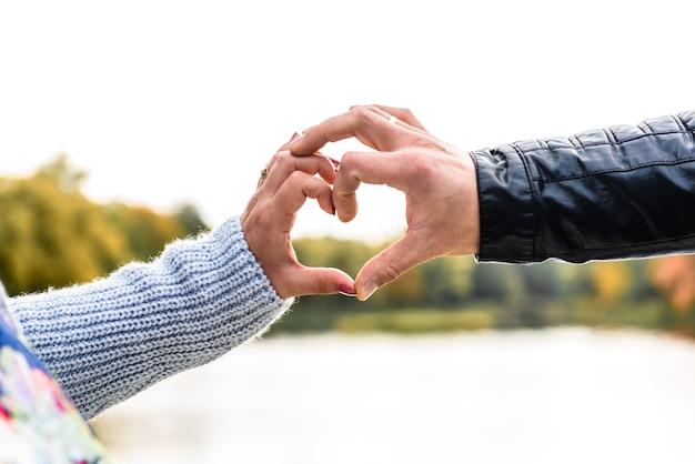 Casal apaixonado fazendo um coração
