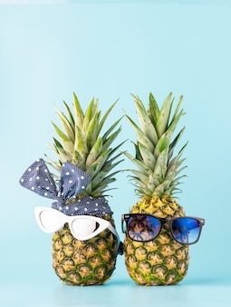 Casal apaixonado, fazer compras em um resort de férias. abacaxi com óculos em forma de um garoto e uma garota em uma luz de fundo