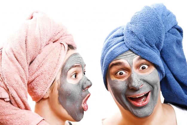Casal apaixonado fez uma máscara facial, homem engraçado e mulher na máscara facial, garota surpresa e cara alegre