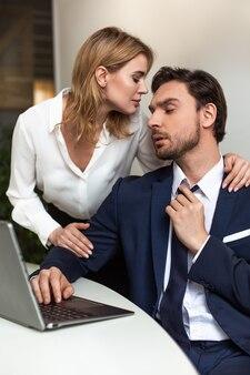 Casal apaixonado flerta no escritório. empresário olha para mulher tocando-o por trás em pé perto do local de trabalho. conceito sedutor.