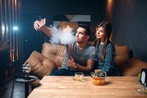 Casal apaixonado fuma narguilé no bar, fumando tabaco e relaxando à noite