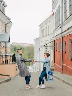 Casal apaixonado girando de mãos dadas, em uma rua da cidade, primavera, vestido com um longo casaco