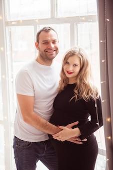 Casal apaixonado grávida abraçando, esperando o bebê