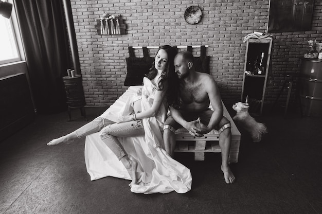 Casal apaixonado grávido deitar na cama afago, à espera de bebé