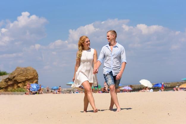 Casal apaixonado homem e mulher caminham na praia de mãos dadas