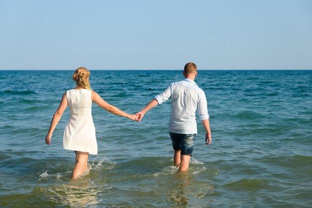 Casal apaixonado homem e mulher entrar e nadar no mar