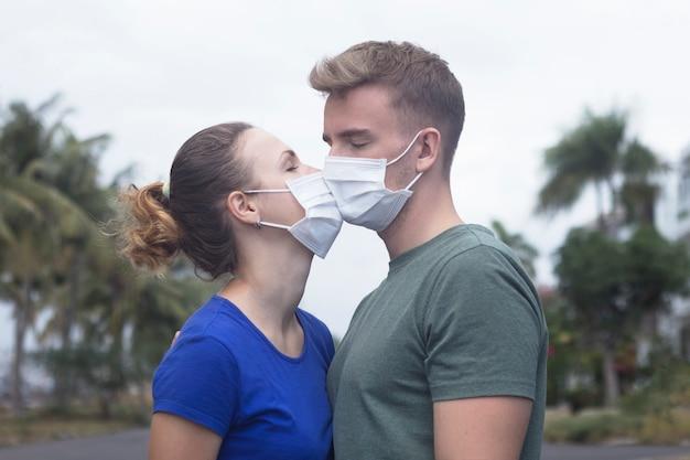 Casal apaixonado, homem e mulher se beijando na máscara protetora médica no rosto na rua asiática. conceito de poluição ambiental. cara, garota contra o coronavírus pandêmico chinês, proteção contra vírus