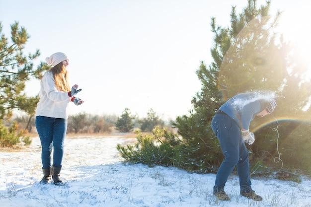 Casal apaixonado joga bolas de neve no inverno na floresta