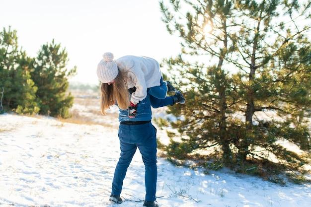 Casal apaixonado joga no inverno na floresta,