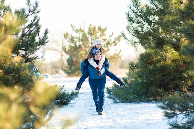 Casal apaixonado joga no inverno na floresta.
