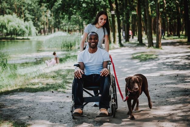Casal apaixonado mulher empurrando a cadeira de rodas para homem