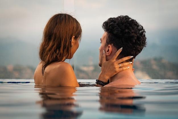 Casal apaixonado na água do pólo infinito durante o pôr do sol. conceito de férias românticas.