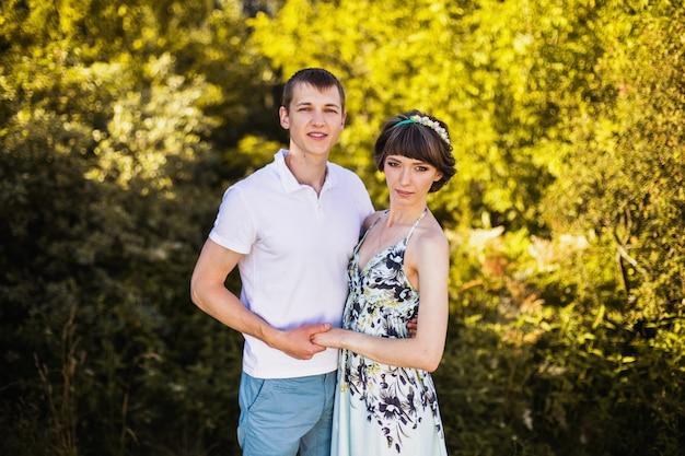 Casal apaixonado na floresta de vidoeiro. homem e mulher caminhando na natureza. abraçando um ao outro. seja feliz. estilo de vida ativo. floresta de verão. luz do sol quente.