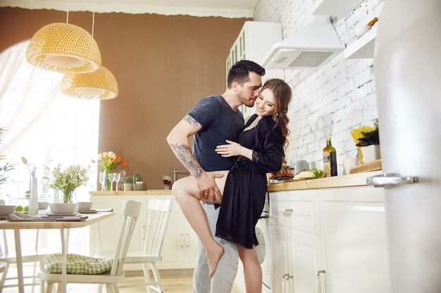 Casal apaixonado na manhã de cozinha abraça e prepara o café da manhã