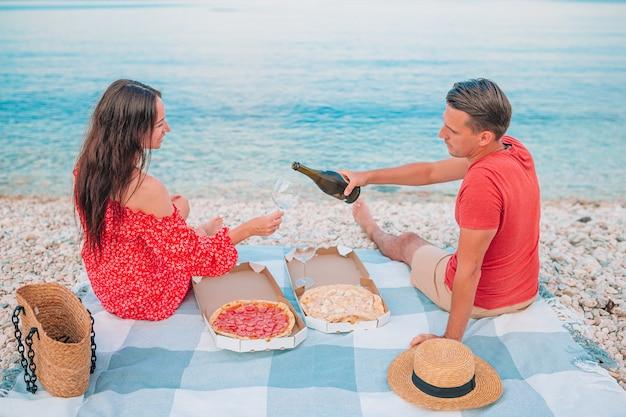 Casal apaixonado na praia fazendo piquenique juntos