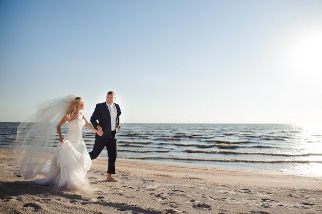 Casal apaixonado na praia no dia do casamento.