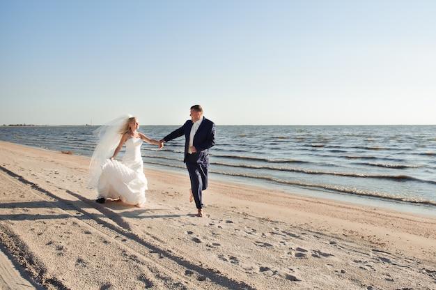 Casal apaixonado na praia no dia do casamento