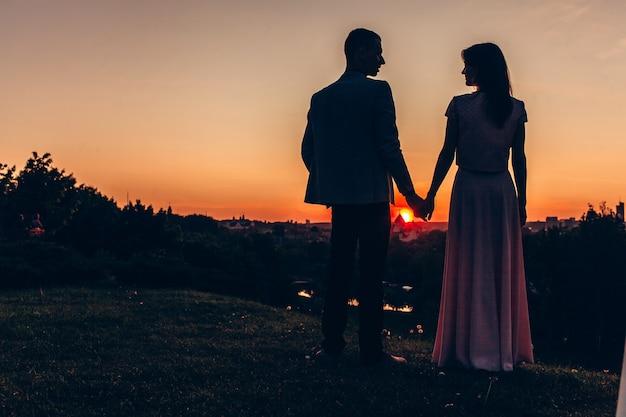 Casal apaixonado na rua durante o pôr do sol