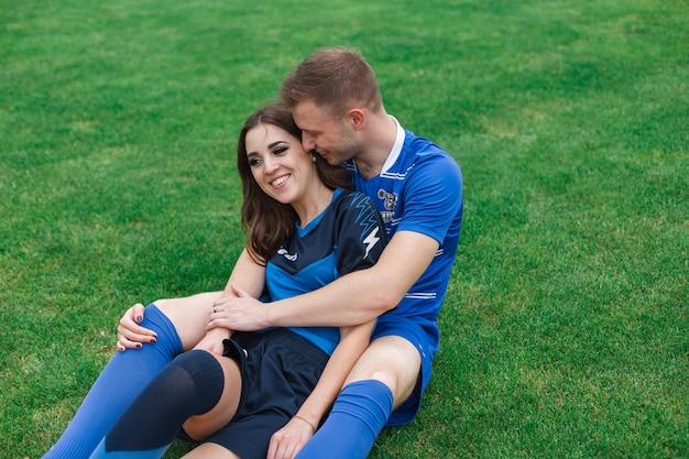 Casal apaixonado no campo de futebol.