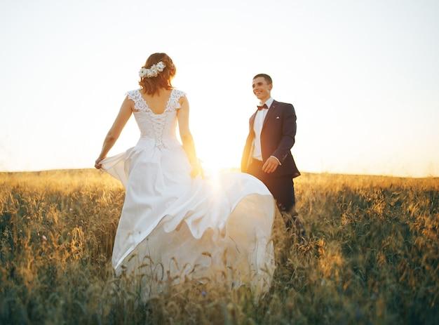 Casal apaixonado no campo de trigo por do sol