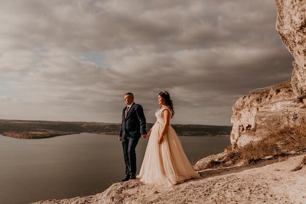 Casal apaixonado no casamento de recém-casados em um vestido e terno branco caminha no verão na montanha acima do rio