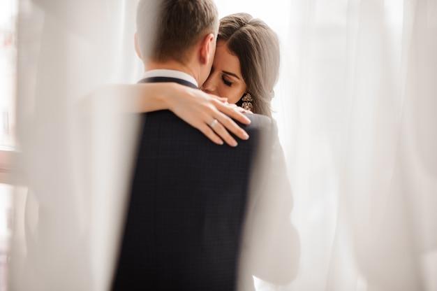 Casal apaixonado - noiva e noivo - abraçando suavemente em uma cena branca