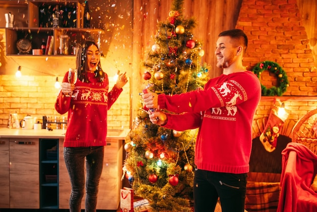 Casal apaixonado, o homem explode um foguete com enfeites, celebração de natal romântica. homem e mulher celebram o natal juntos
