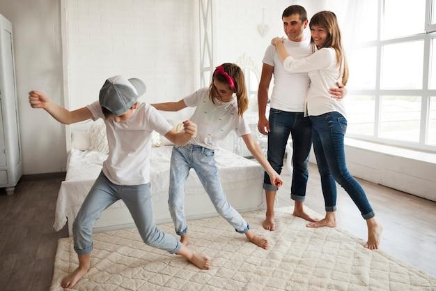 Casal apaixonado olhando para a dança de seus filhos em casa