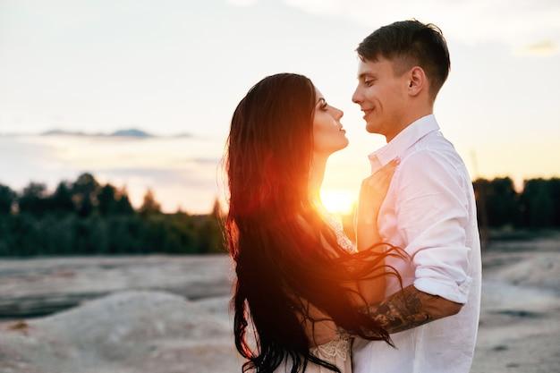 Casal apaixonado olhando um ao outro ao pôr do sol