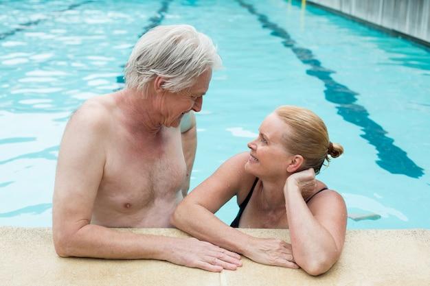 Casal apaixonado olhando um para o outro enquanto se inclinam à beira da piscina