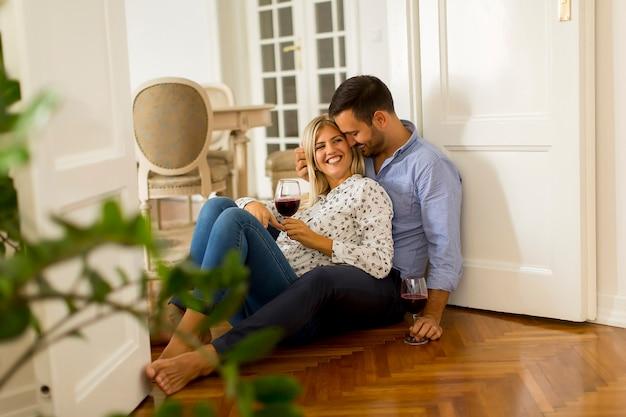 Casal apaixonado olhando uns aos outros enquanto bebe vinho tinto no chão