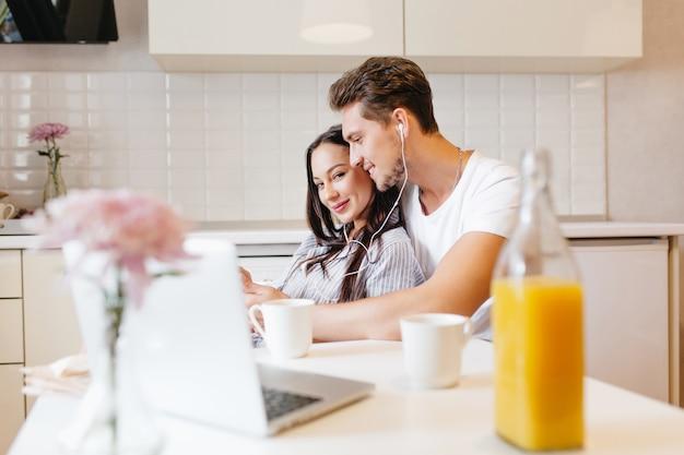 Casal apaixonado ouvindo música durante o café da manhã em uma cozinha aconchegante