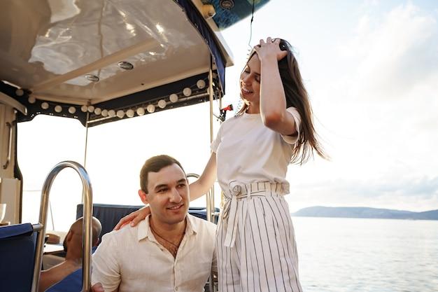 Casal apaixonado passando um tempo em um iate no mar