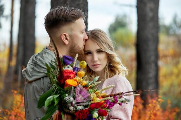 Casal apaixonado percorre a floresta de outono. abraços e beijos de homens e mulheres, relacionamentos e amor. jovem casal fica na grama vermelha amarela, um buquê de flores na mão da menina
