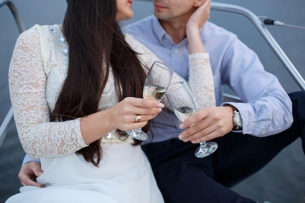 Casal apaixonado por copos de vinho decorados no dia do casamento. dois copos com champanhe nas mãos dos noivos ao ar livre. o homem e a mulher mantêm os vidros de vinho perto. local de comemoração.