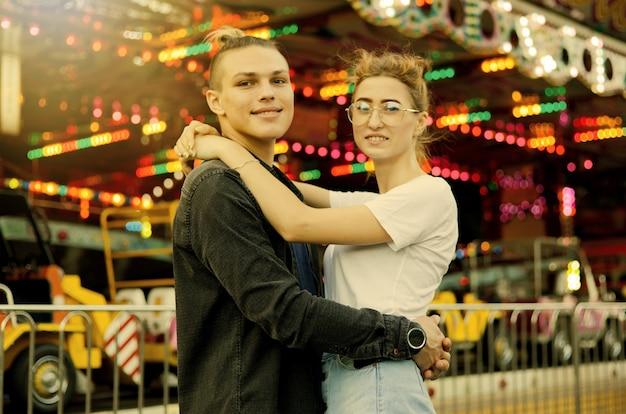 Casal apaixonado posando em parque de diversões
