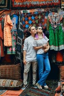 Casal apaixonado posando no mercado de tapetes do leste