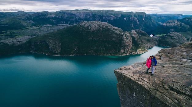 Casal apaixonado preikestolen enorme penhasco (noruega, lysefjorden, manhã, manhã, vista)