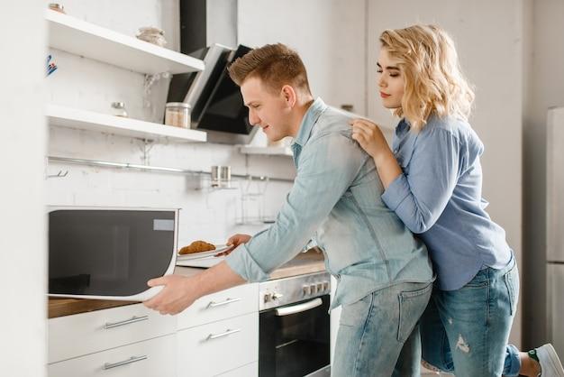 Casal apaixonado prepara comida para o jantar romântico.