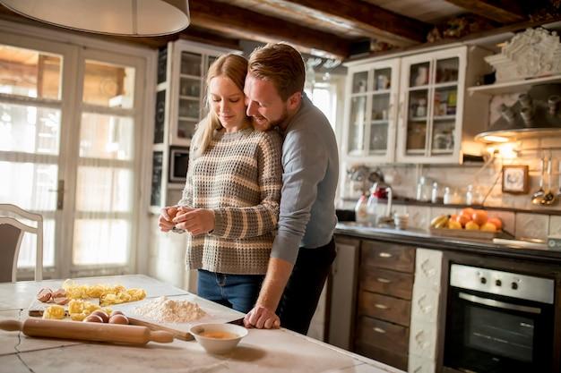 Casal apaixonado preparar macarrão na cozinha