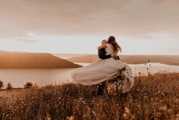 Casal apaixonado, recém-casados de vestido branco e terno, abraço e beijo giro na grama alta em campo de verão na montanha acima do rio