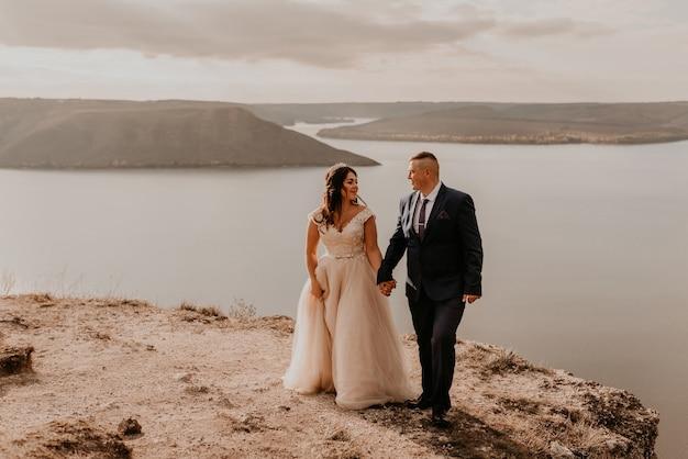 Casal apaixonado, recém-casados de vestido branco e terno andam no verão na montanha acima do rio. pôr do sol e nascer do sol