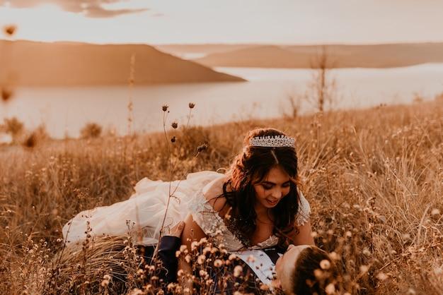 Casal apaixonado, recém-casados em um vestido branco e terno está andando deitado no campo de grama alta no verão