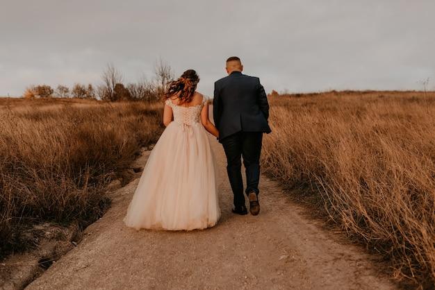 Casal apaixonado, recém-casados em um vestido e terno branco estão caminhando na grama alta em um campo no verão