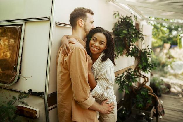 Casal apaixonado se abraça em rv, acampando em um trailer. homem e mulher viajando em van, férias em autocaravana, lazer para campistas em carro de campismo