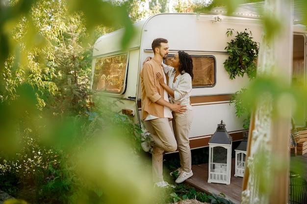 Casal apaixonado se abraça em rv, acampando em um trailer. homem e mulher viajando em van, férias românticas em motorhome, lazer para campistas em carro de camping