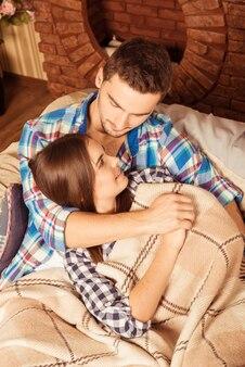 Casal apaixonado se abraçando e deitado no sofá