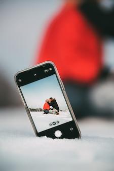 Casal apaixonado se abraçando e se beijando enquanto tira uma selfie no celular colocado na neve no campo
