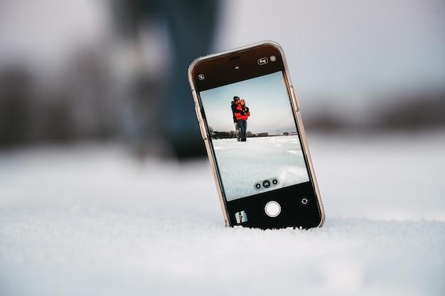 Casal apaixonado se abraçando enquanto tira uma selfie no celular colocado na neve no campo