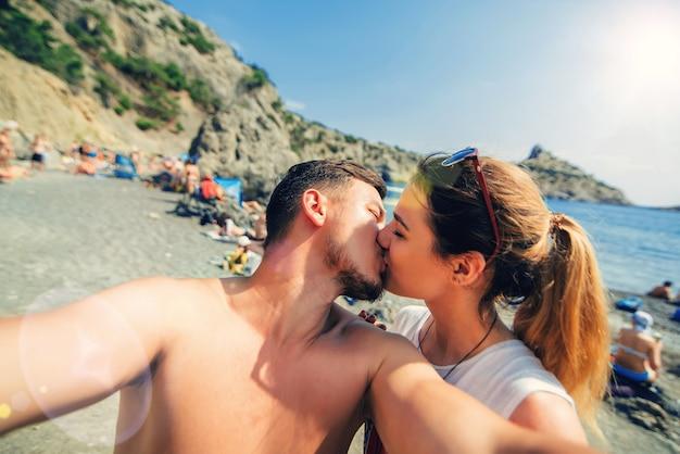 Casal apaixonado se beijando e tirando selfies ao telefone na praia